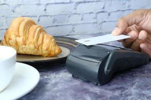 conceito de pagamento sem contato com jovem pagando com cartão de crédito foto