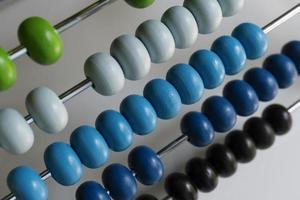 ábaco com contas verdes azuis, brancas e pretas
