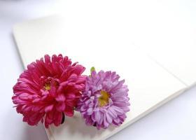 caderno em branco com flor rosa e roxa foto