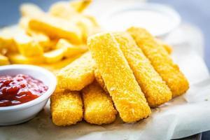 dedo de peixe e batatas fritas com ketchup de tomate e molho de maionese foto