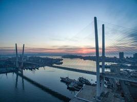 Ponte Zolotoy e água contra o céu nublado do pôr do sol em Vladivostok, Rússia foto