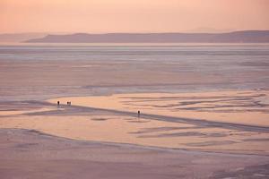 silhueta de pessoas caminhando sobre o gelo na baía de amur em vladivostok, Rússia foto