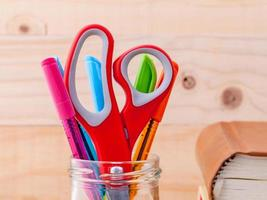 close-up de tesouras e canetas em um copo