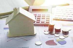pilha de moedas e uma casa modelo
