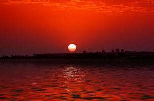 pôr do sol sobre o horizonte da cidade por corpo de água foto