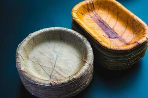 pilha de pratos de papel ecologicamente corretos biodegradáveis ao lado de uma pilha de tigelas feitas de folhas