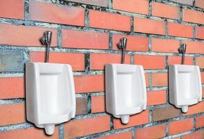 três mictórios contra parede de tijolos foto