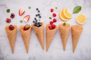 frutas e casquinhas de sorvete em um fundo cinza claro