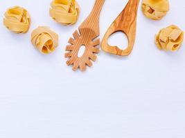 macarrão e utensílios de madeira com espaço de cópia foto
