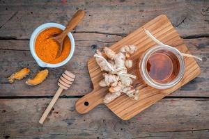 pó de curcumina, mel e raízes de curcumina na velha mesa de madeira