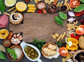 placa de madeira rodeada de ingredientes frescos foto