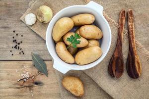 batatas frescas orgânicas em uma tigela de cerâmica branca com ervas foto