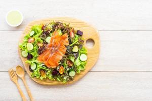salmão defumado cru com salada de vegetais verdes frescos foto