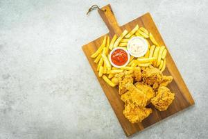 asas de frango com batata frita, ketchup e maionese