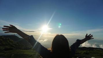 mulher com os braços estendidos no topo da montanha com céu azul nublado
