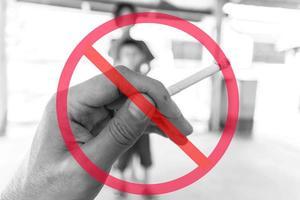 sinal de proibição geral sobreposto à mão segurando o cigarro com crianças desfocadas no fundo
