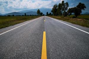 listras amarelas na estrada que atravessa campos e árvores em ambos os lados com montanhas e céu azul nublado foto