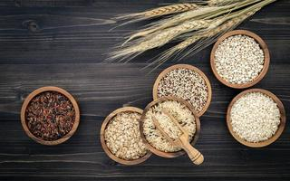 grãos em tigelas em um fundo escuro de madeira