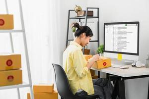 mulher verificando pedidos online e caixas de embalagem