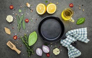frigideira de ferro fundido com ingredientes frescos em um fundo de pedra escura