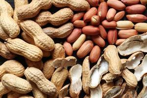 amendoins inteiros, descascados e cascas vazias foto