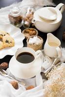 xícara de café, pires e servidor de creme ao lado de bolos na toalha de mesa amarrotada foto