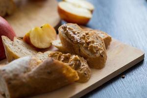 Maçãs fatiadas com baguete fatiada com manteiga de chocolate na placa de madeira em uma mesa de madeira escura