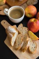 maçãs inteiras e fatiadas com baguete fatiada em uma placa de madeira com uma xícara de café em uma mesa de madeira escura