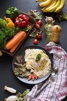macarrão carbonara com bacon e parmesão, alface e tomate fatiado em um prato preto foto