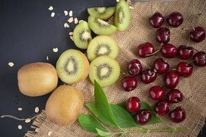 cerejas e fatias de kiwi na serapilheira e na mesa de madeira escura foto