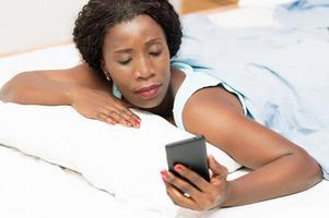 mulher na cama olhando para um telefone celular