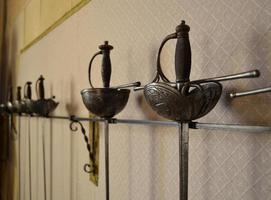 espadas penduradas na parede para exibição foto