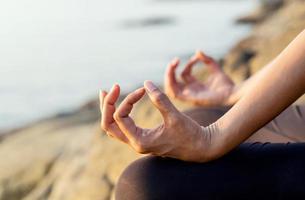 close-up das mãos de uma mulher em meditação