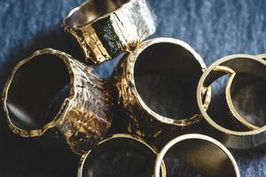 vários anéis de ouro empilhados em uma placa de ardósia