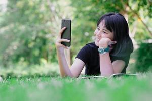 uma menina sentada no jardim com seu telefone foto