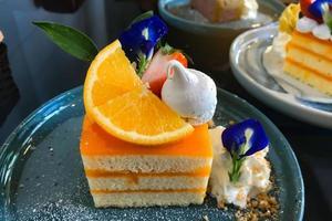 Bolo de laranja com cobertura de laranja no prato pronto para comer foto