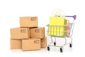 caixas de papel e sacolas de compras em um carrinho em um fundo branco. conceito de compras online ou e-commerce e conceito de serviço de entrega