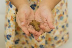 as mãos de uma criança com uma cruz cristã de madeira foto