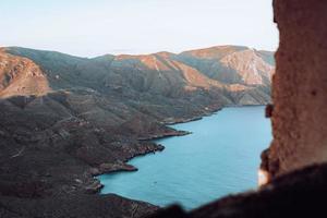 montanhas marrons e verdes ao lado da massa de água durante o dia