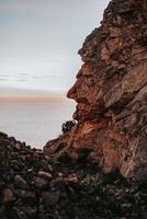formação de rocha marrom perto do corpo d'água durante o dia foto