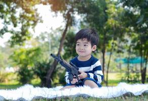 menino asiático sentado em um parque em uma manhã clara segurando uma arma de brinquedo foto