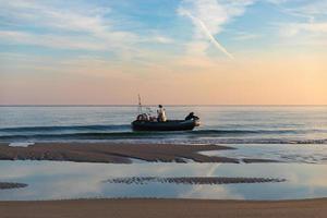 polônia 2018 - homem viaja por mar em um barco inflável durante o nascer do sol