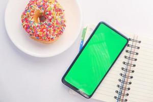 donut e telefone inteligente com tela verde na mesa foto