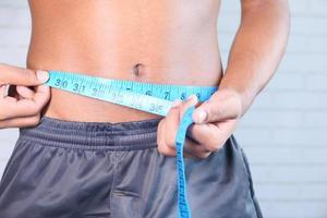 jovem medindo a cintura com uma fita métrica foto