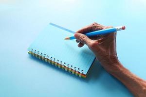mão escrevendo no bloco de notas