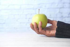 mão segurando uma maçã verde no fundo branco