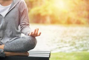 jovem mulher de ioga meditando e relaxando na natureza foto