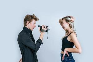 retrato feliz de casal segurando uma câmera de vídeo e gravando um vídeo foto