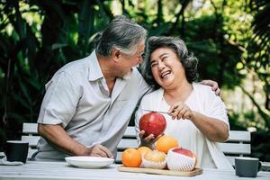 casal de idosos fatiando e comendo frutas foto