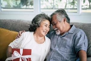casal de idosos surpreende com caixa de presente na sala de estar foto